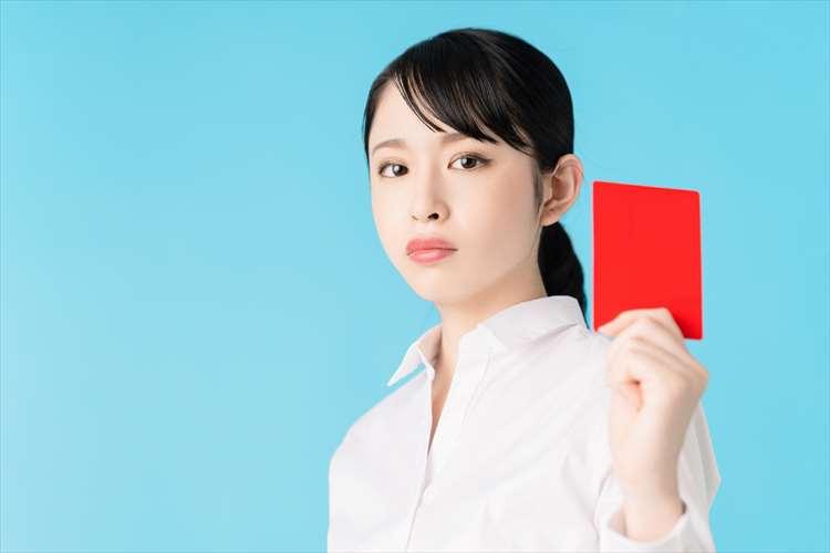 女性がレッドカードを出している画像