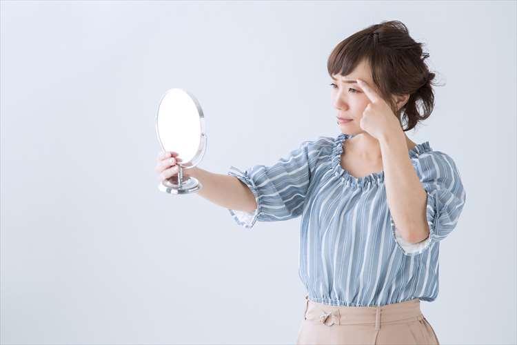眉に指をあてて鏡を見ている画像