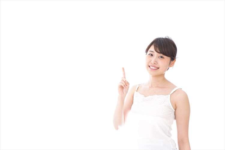人差し指を立て笑顔の女性
