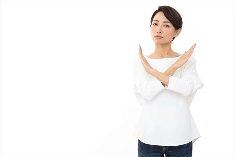 バツ印を腕で示している女性