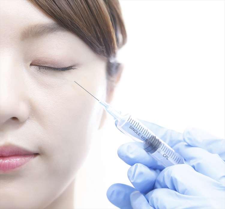 女性の頬に注射をしようとしている画像