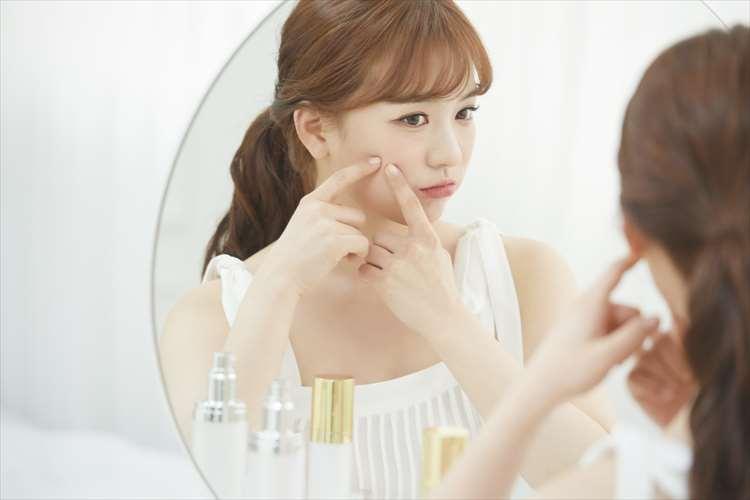 女性が顔の気になる部分を指で触っている画像