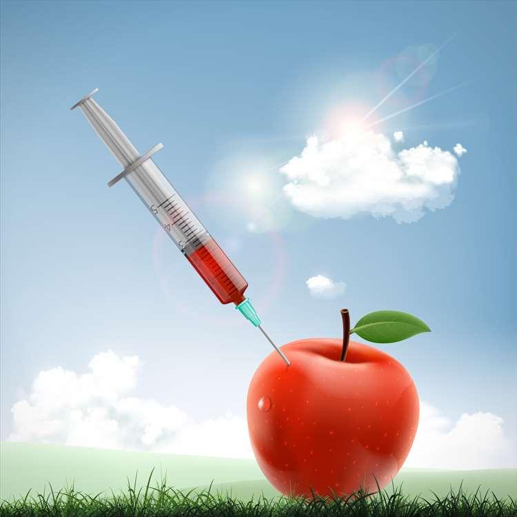 一個注射器的圖像有紅色液體的困在蘋果