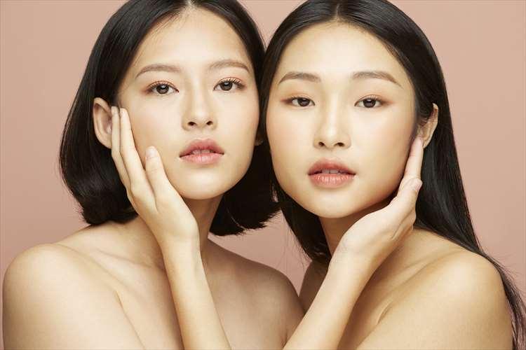 用他們的雙手在臉頰上看著你的兩個女人的形象