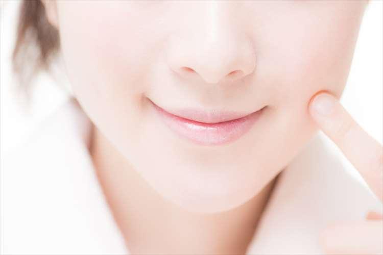 指を頬にあてた女性の画像