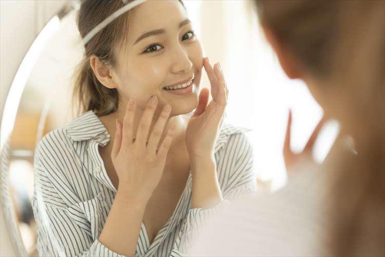 鏡に向かって笑顔を浮かべる女性